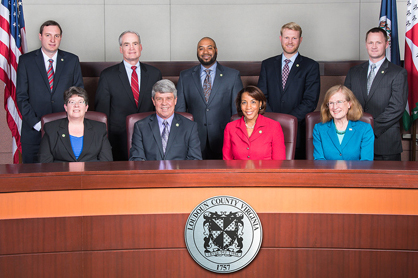 Nine members of the board of supervisors behind wooden desk