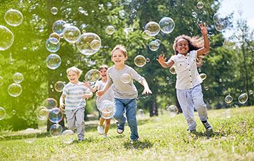 image of children playing in a park with bubbles